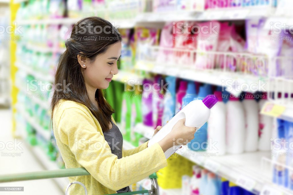 Asian woman buys in the supermarket laundry detergent stock photo