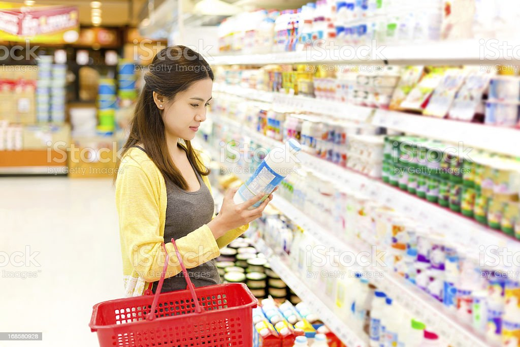Asian woman buys in the supermarket milk. royalty-free stock photo