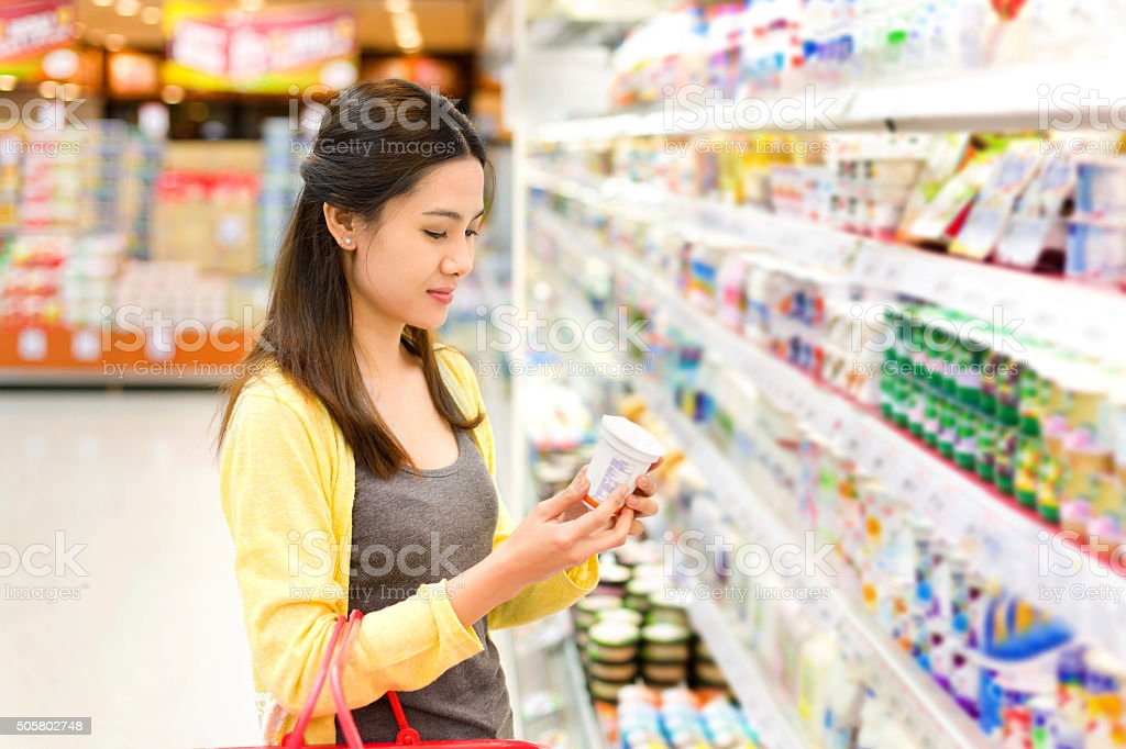 Asian woman buys in the supermarket yogurt stock photo