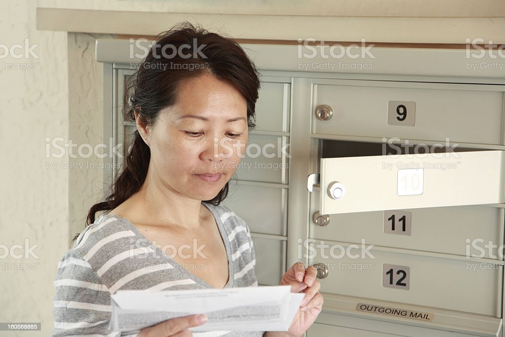 Asian woman checking her mailbox stock photo