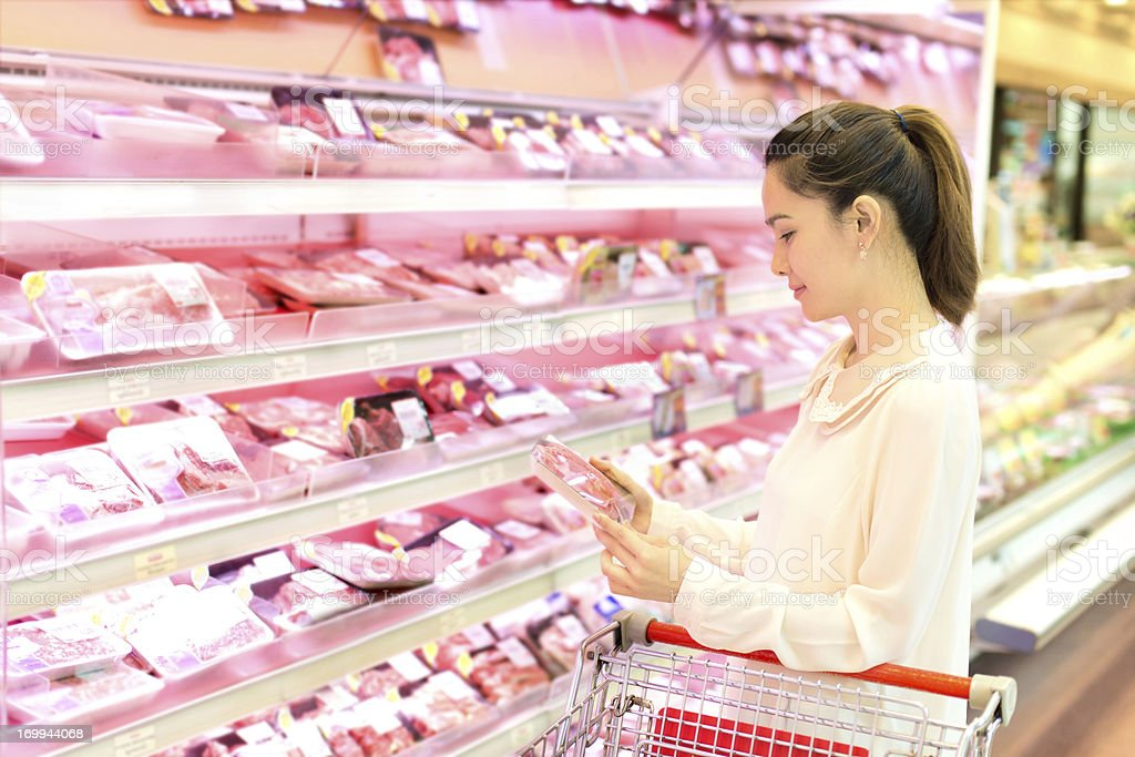 Asian woman chooses meat in the store. stock photo
