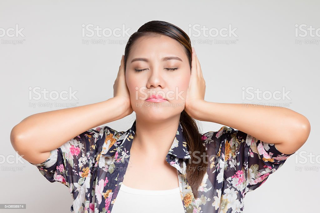 Asian woman covers his ears with his hands stock photo