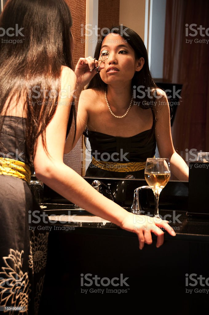 Asian Woman Curling Her Eyelashes in front of Vanity Mirror stock photo