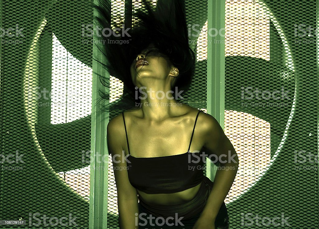 Asian woman dancing infront of industrial fan. royalty-free stock photo