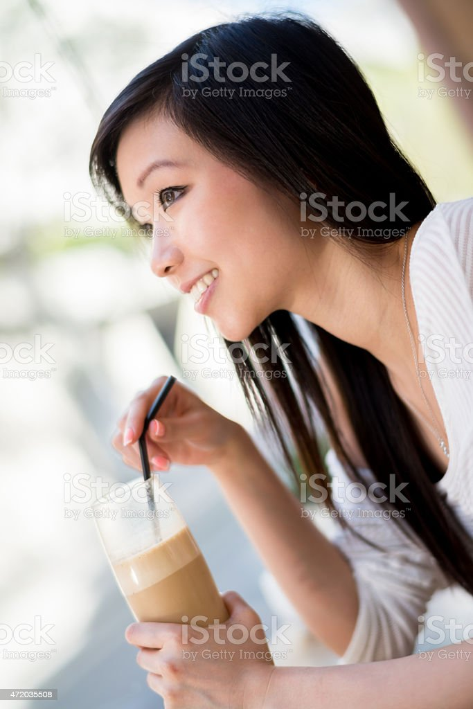 Asian woman drinking a frappuccino at a cafe stock photo
