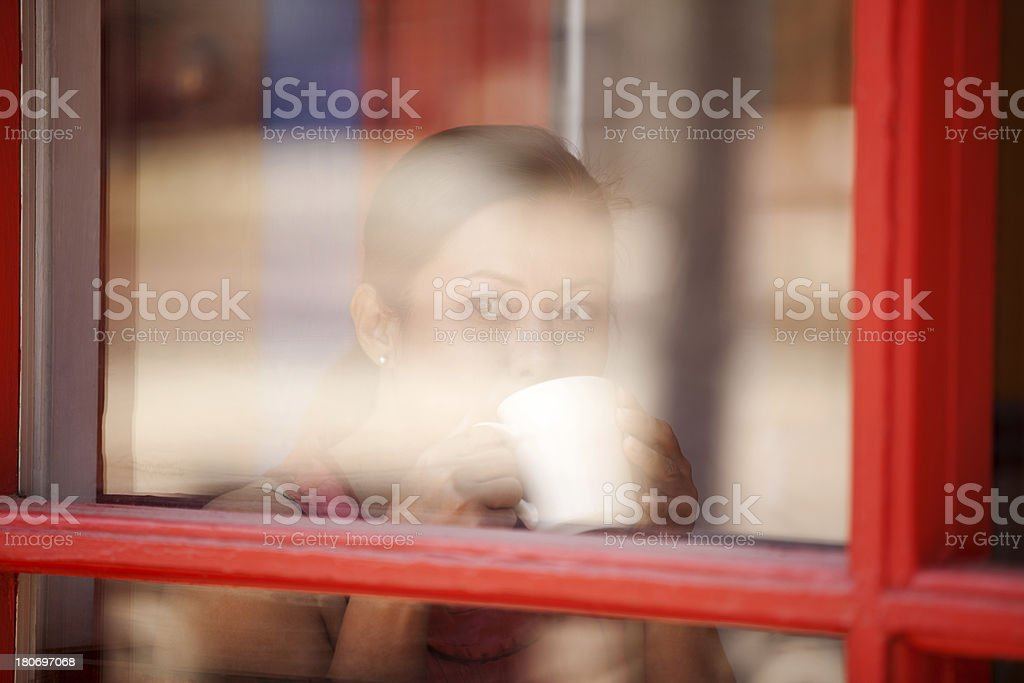 Asian Woman Drinking Coffee Behind a Glass Window royalty-free stock photo