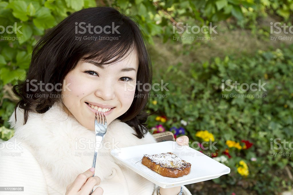 Asian Woman Eating French Toast in Park royalty-free stock photo