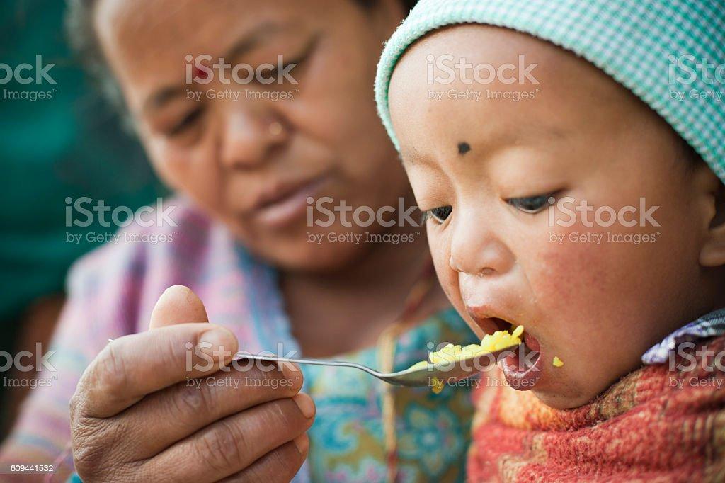 Asian woman feeding food to little child. stock photo