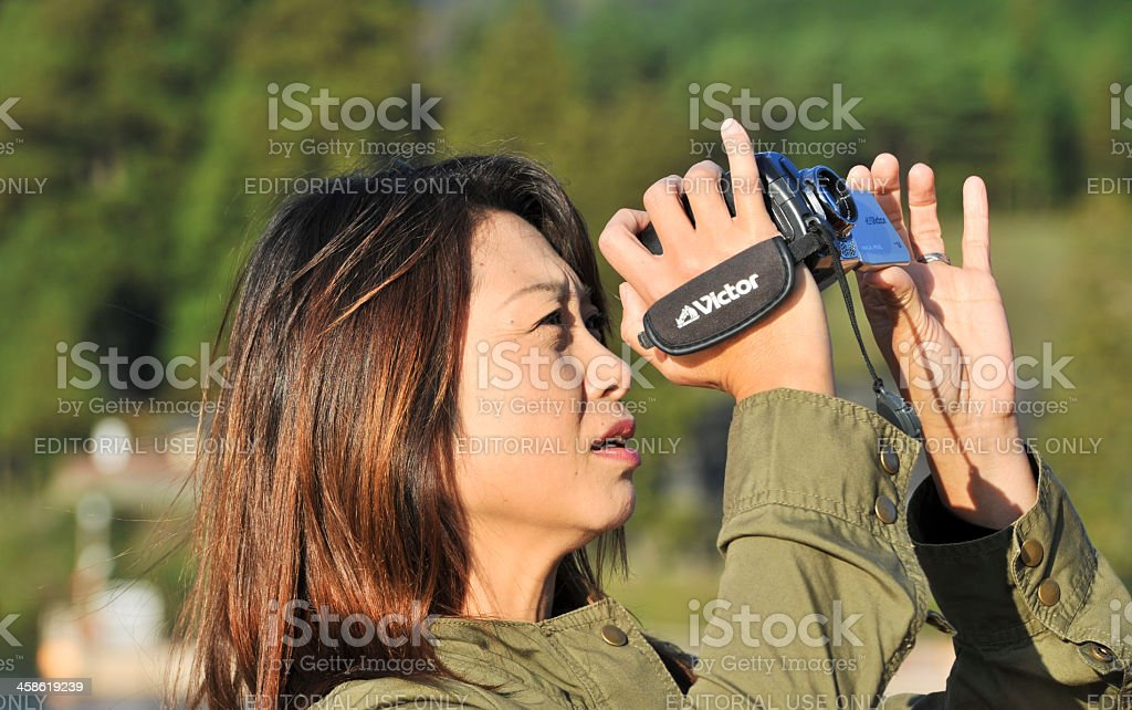 Asian woman filming with JVC camcorder. stock photo