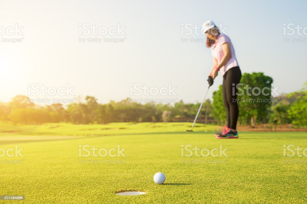 Asian woman golfer putting on green for birdie stock photo