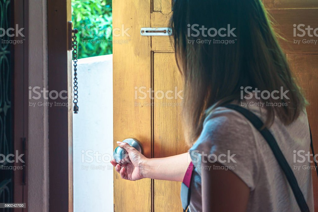 Asian woman grabbing knob opening wooden door stock photo