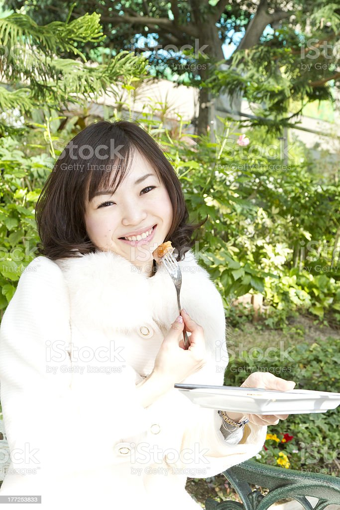 Asian Woman Happily Eating French Toast in Park royalty-free stock photo