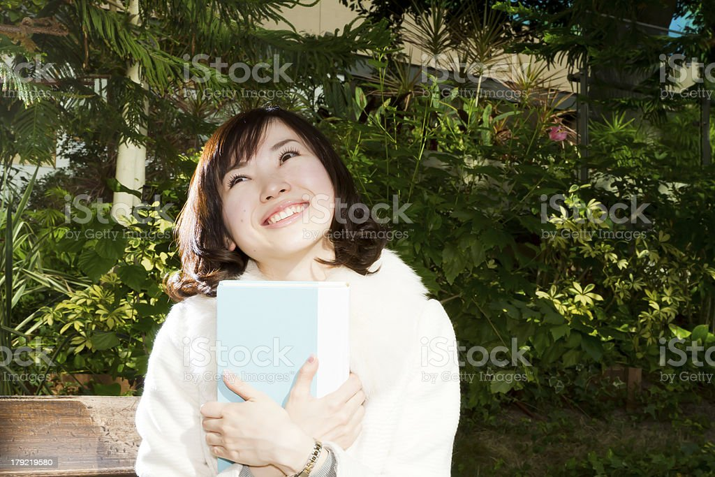 Asian Woman Happily Holding Book royalty-free stock photo