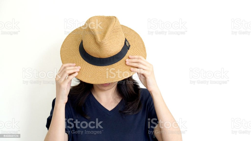 Asian woman hide face behind hat. Introvert and antisocial conce stock photo