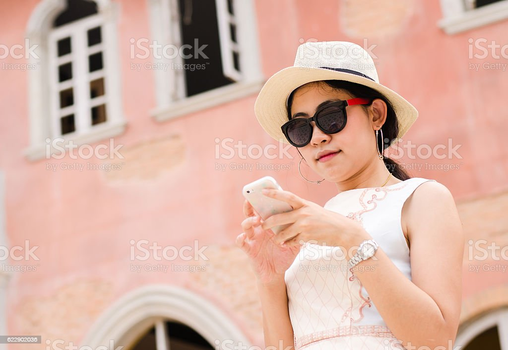 Asian woman hipster traveler using phone with fashion vintage sunset stock photo