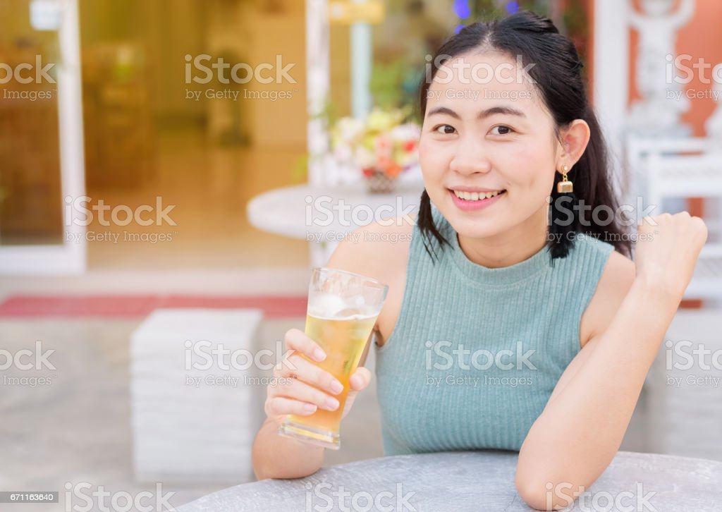 Asian woman holding glass of beer in summer lifestyle stock photo