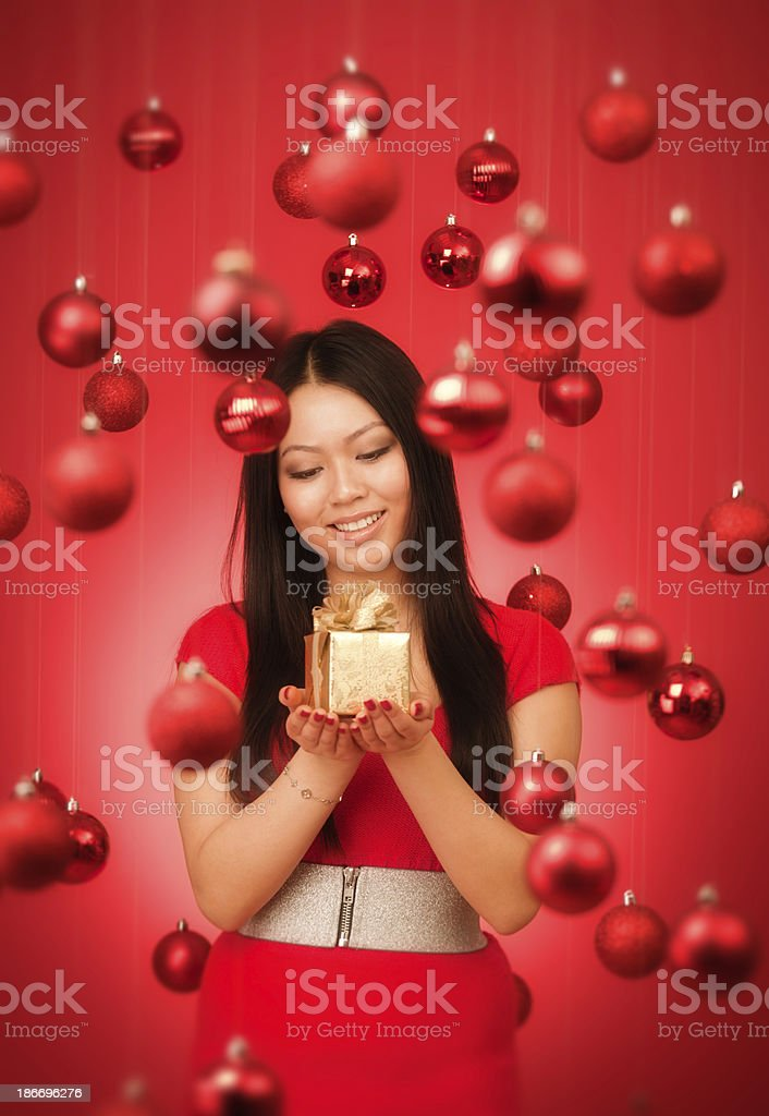 Asian Woman Holding Present with Red Christmas Theme Background royalty-free stock photo