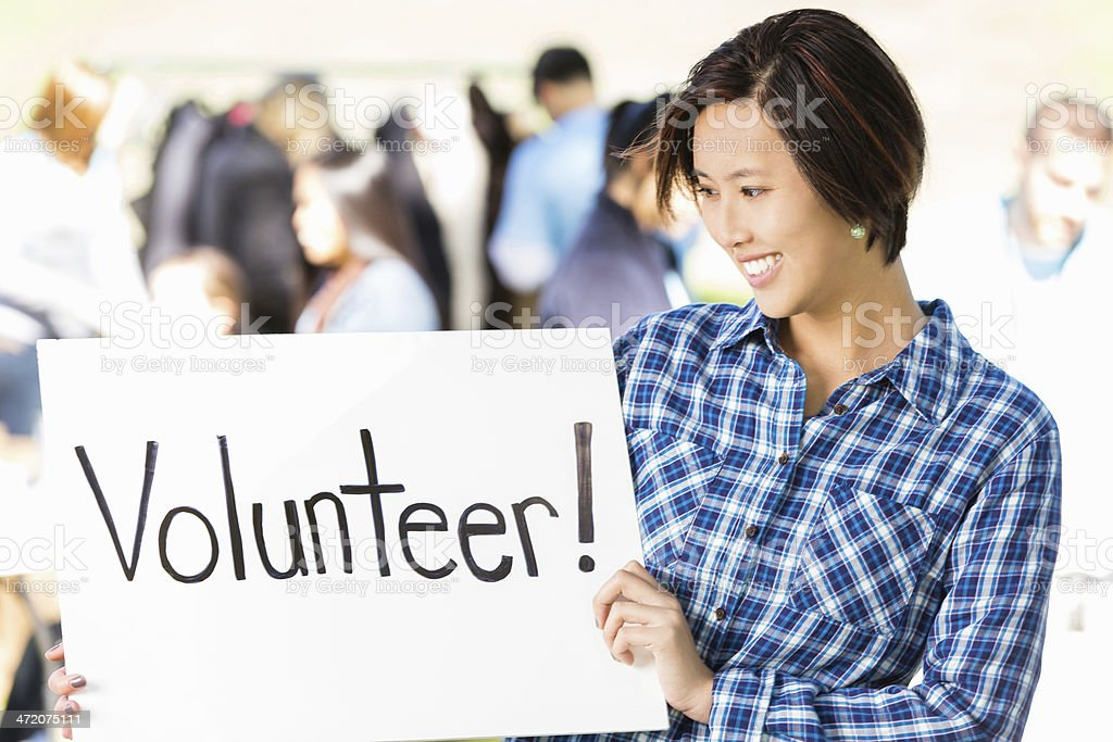 Asian woman holding 'volunteer' sign at outdoor drive stock photo
