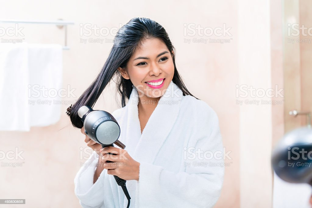 Asian woman in bathroom drying hair stock photo