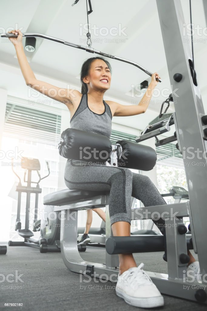 Asian woman in sportswear exercising with exercise machine at the gym. stock photo