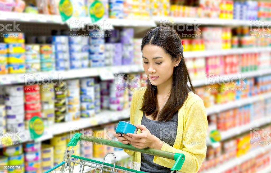 Asian woman in the supermarket to buy canned stock photo