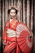 asian woman in traditional red kimono with parasol