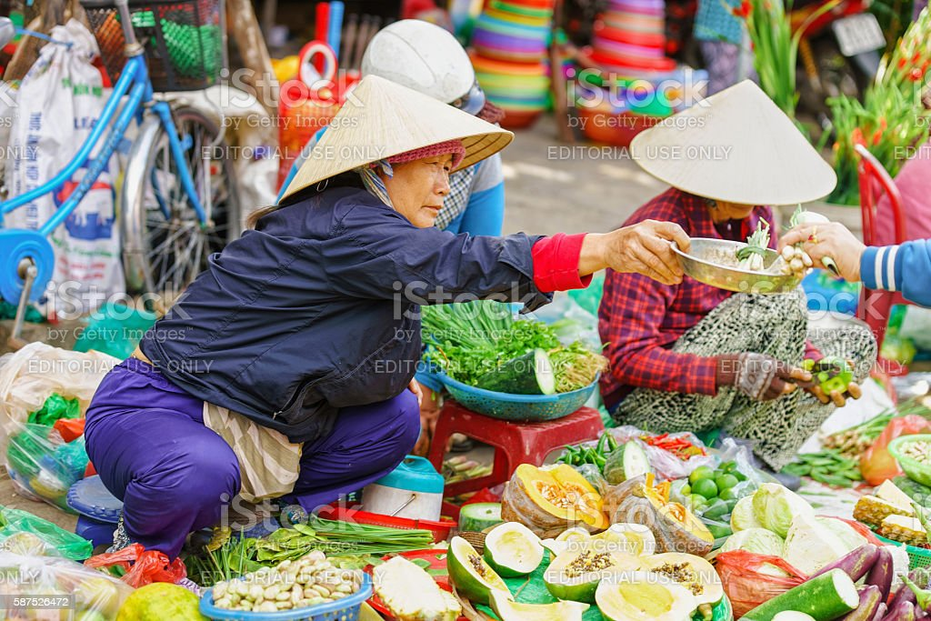 Asian woman in traditional vietnamese hats selling fresh vegetables stock photo