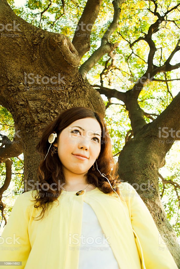 Asian woman, listening to music under a tree stock photo
