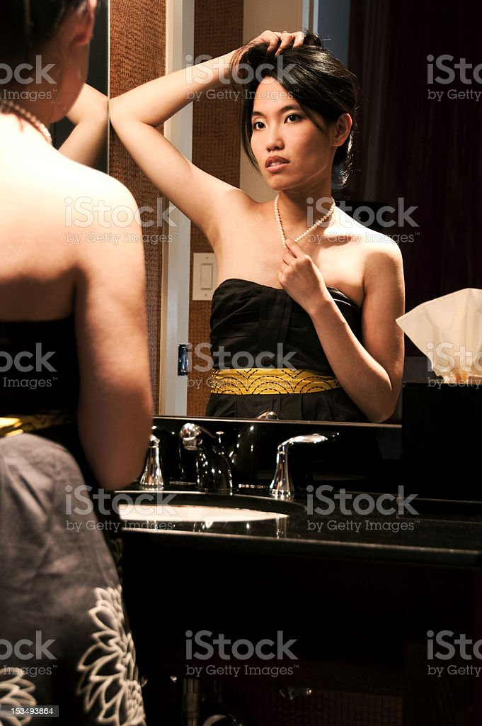 Asian Woman Looking at Herself in Vanity Mirror royalty-free stock photo