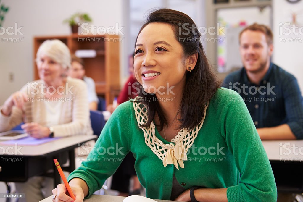 Asian woman looking at the board in an adult education stock photo