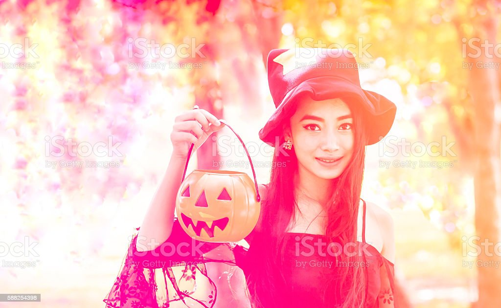 Asian woman on black dress and holding plastic pumpkin doll stock photo