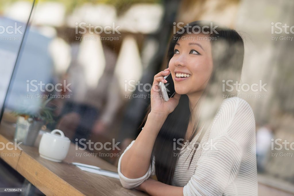 Asian woman on the phone at a cafe stock photo