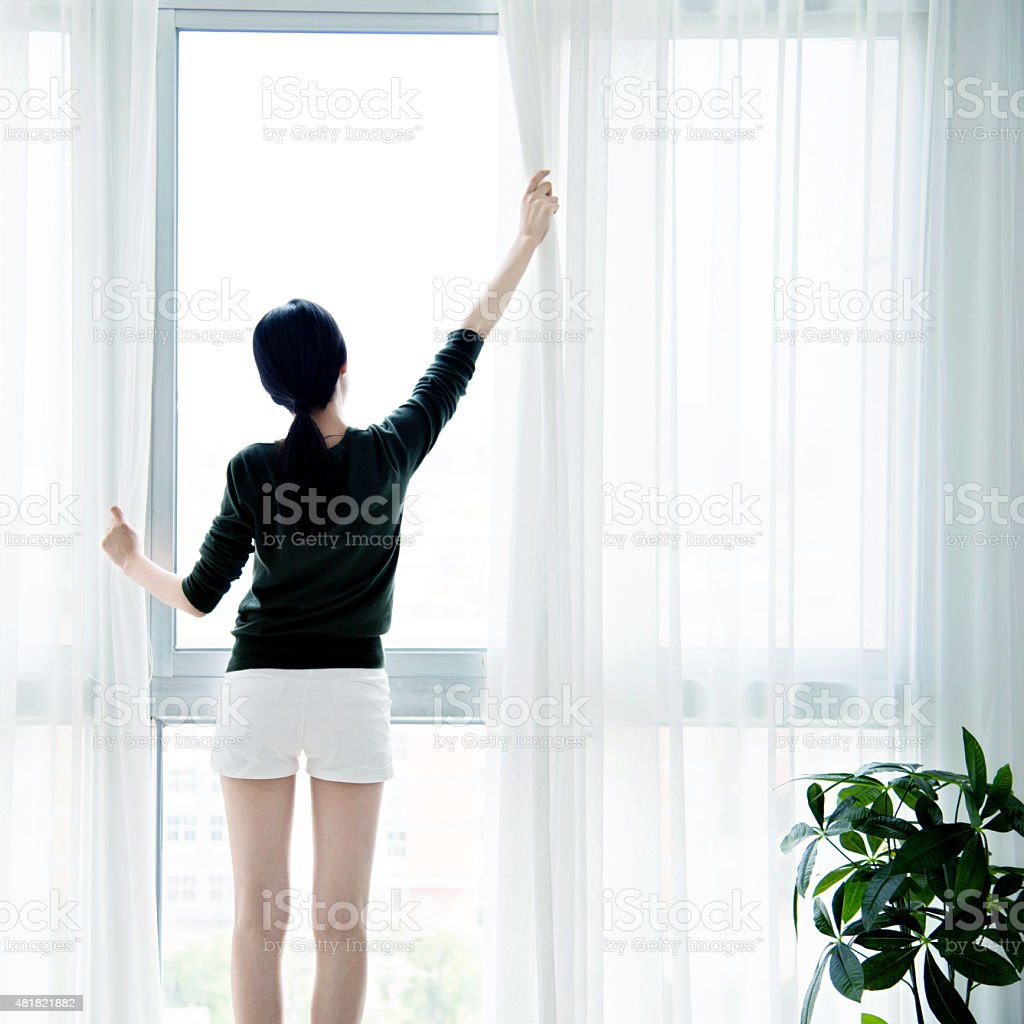 Asian woman open curtains stock photo