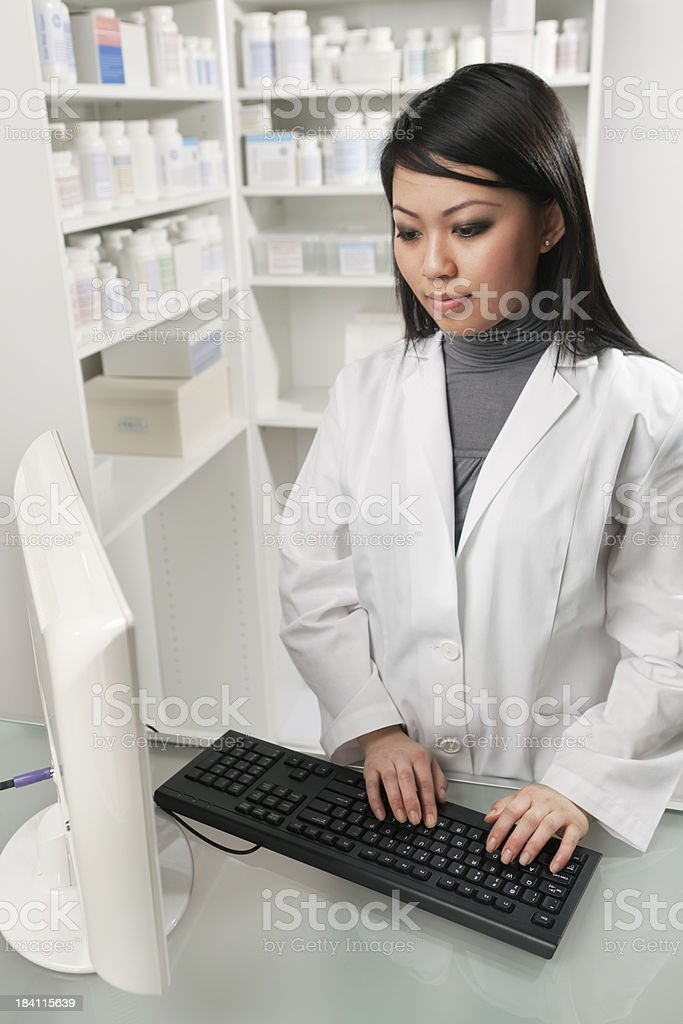 Asian Woman Pharmacist in Retail Pharmacy Working Vt royalty-free stock photo