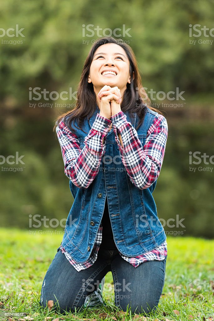 Asian Woman Praying in a Park stock photo