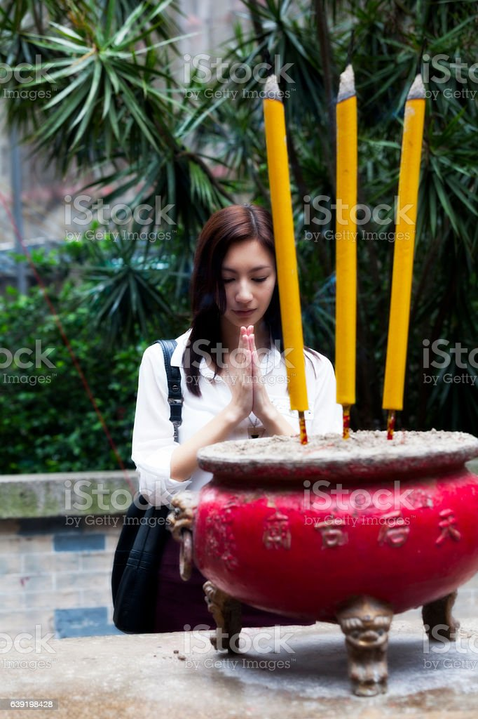 Asian woman praying with incense stock photo
