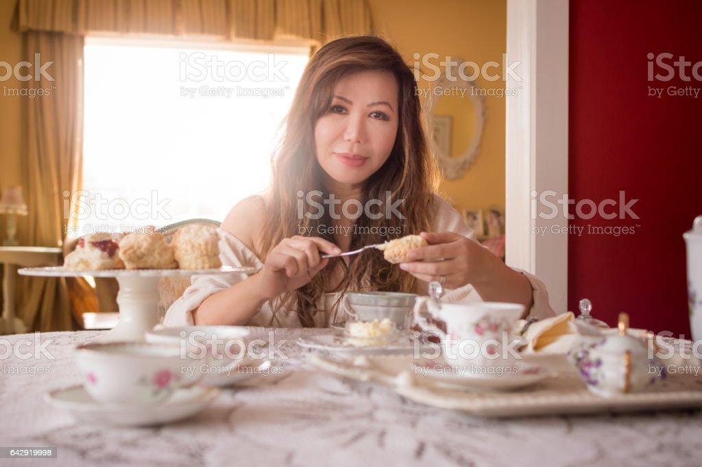 Asian woman preparing tea and scones at home stock photo