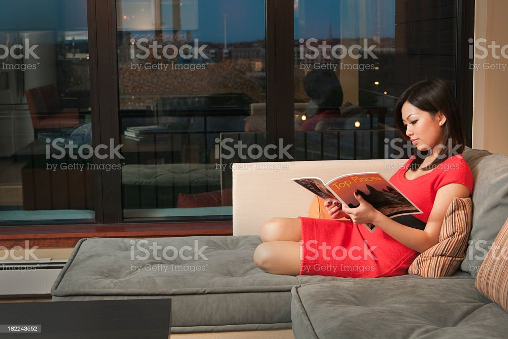 Asian Woman Reading Magazine on Sofa, Inside Apartment at Night royalty-free stock photo