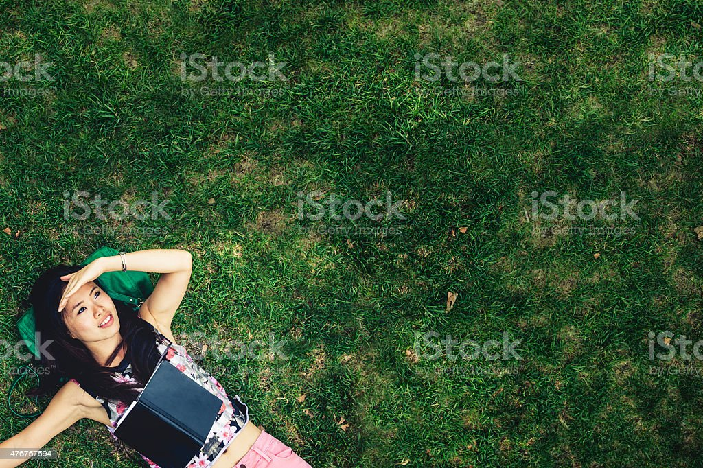 Asian woman relaxed laying down in the park stock photo