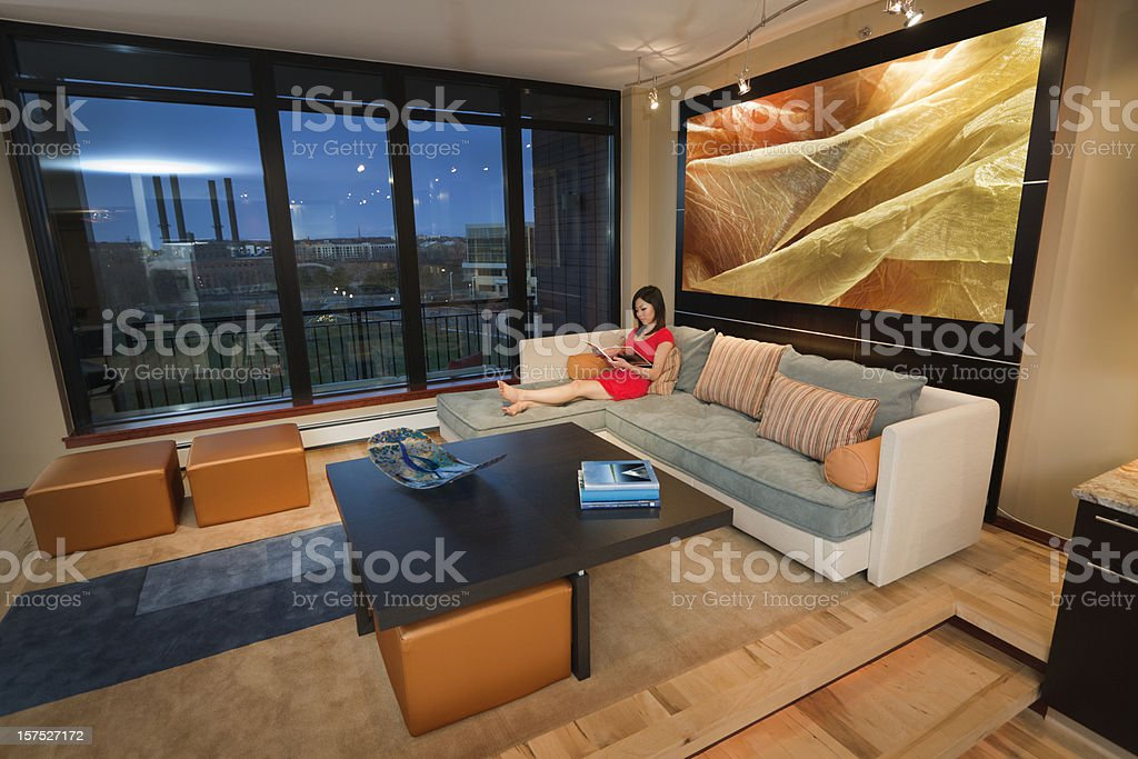 Asian Woman Relaxing in Modern Condominium Apartment Residential Home Interior royalty-free stock photo