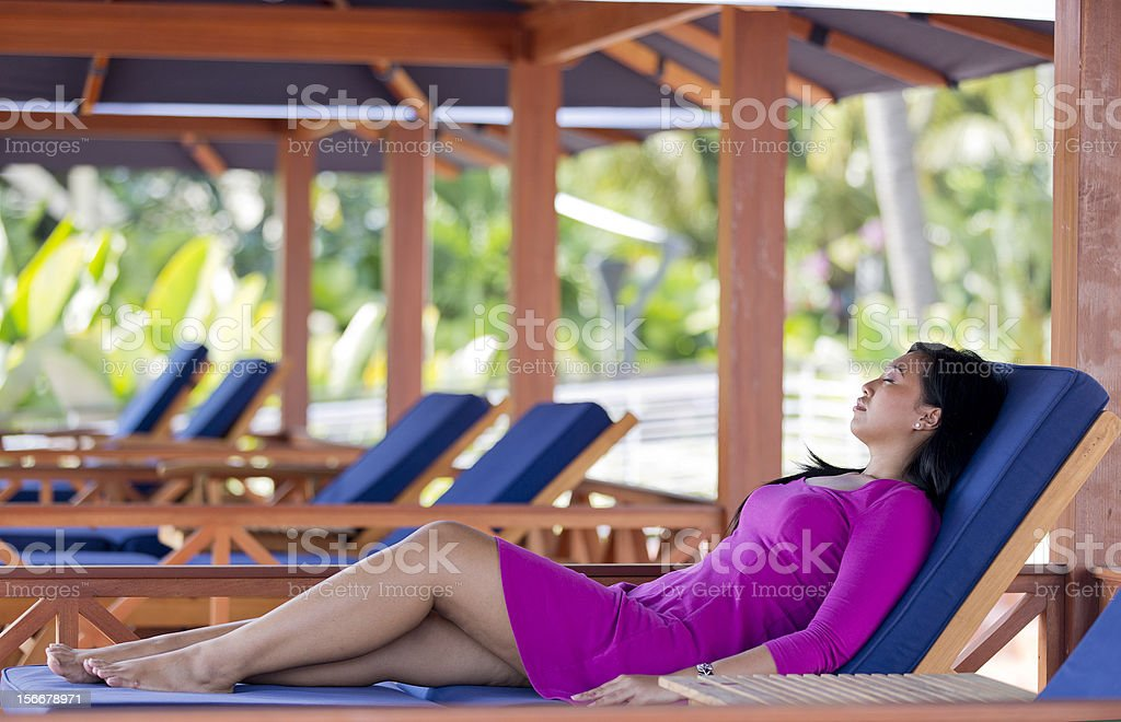 Asian woman relaxing on a deck chair royalty-free stock photo