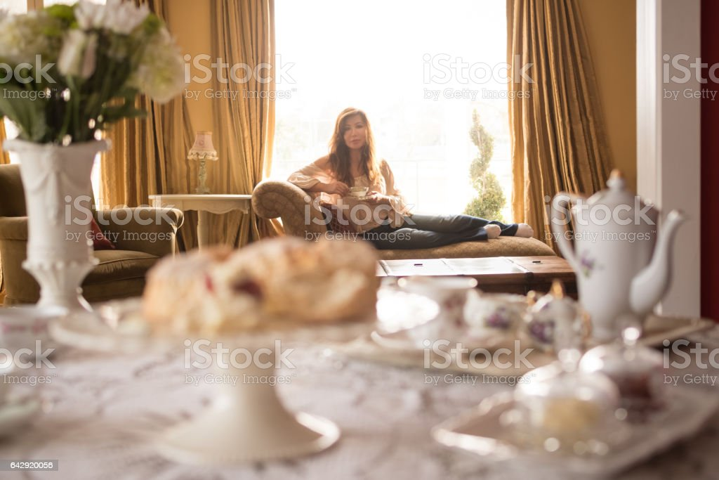 Asian woman relaxing on chaise lounge drinking tea stock photo