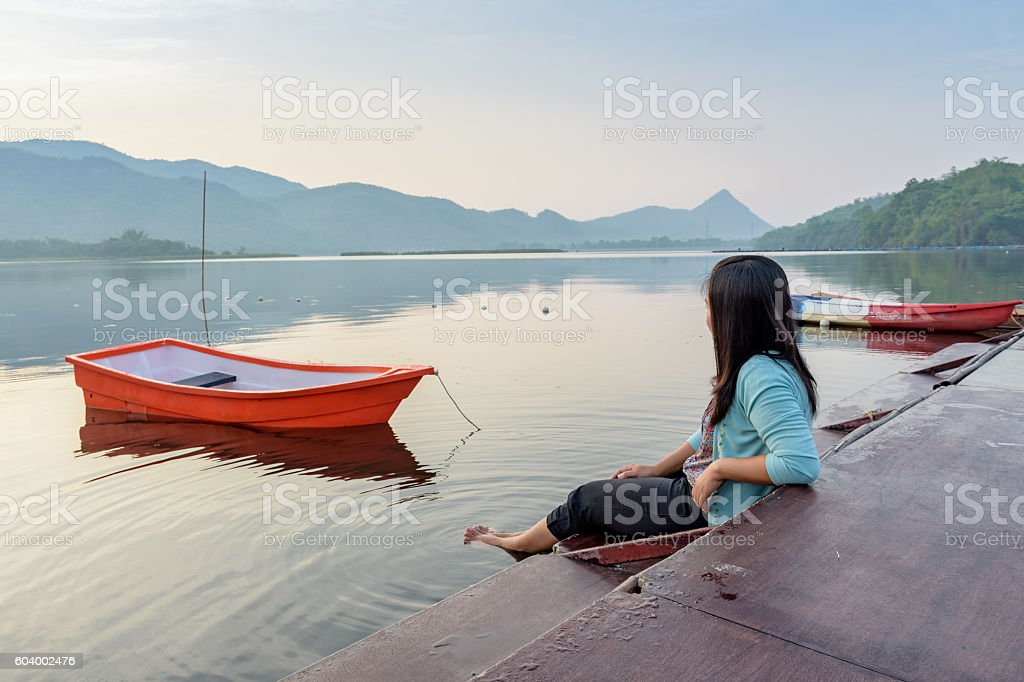Asian woman relaxing on wooden port of lake royalty-free stock photo