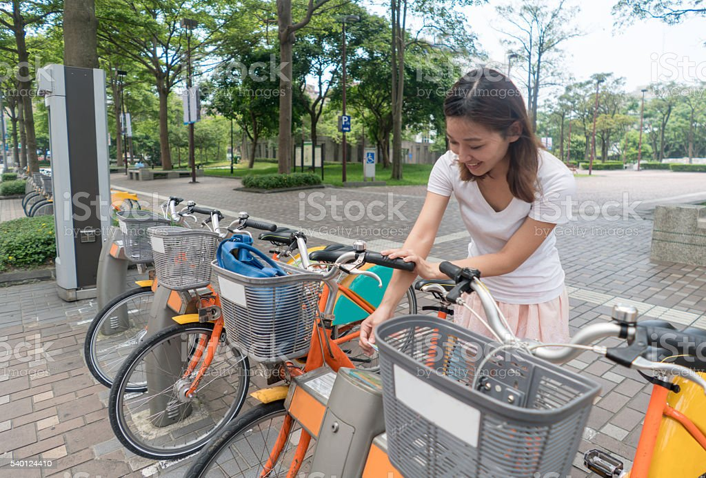 Asian woman renting a bike in Hong Kong stock photo