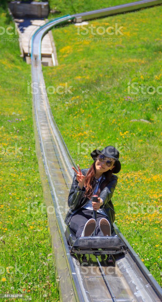 Asian woman riding summer toboggan (sled) down a hill through the beautiful flower meadow in Oeschinensee, Kandersteg, Switzerland. Toboggan is a simple sled, proposing further enjoyment and excitement following a refreshing trip to the mountain lake. stock photo