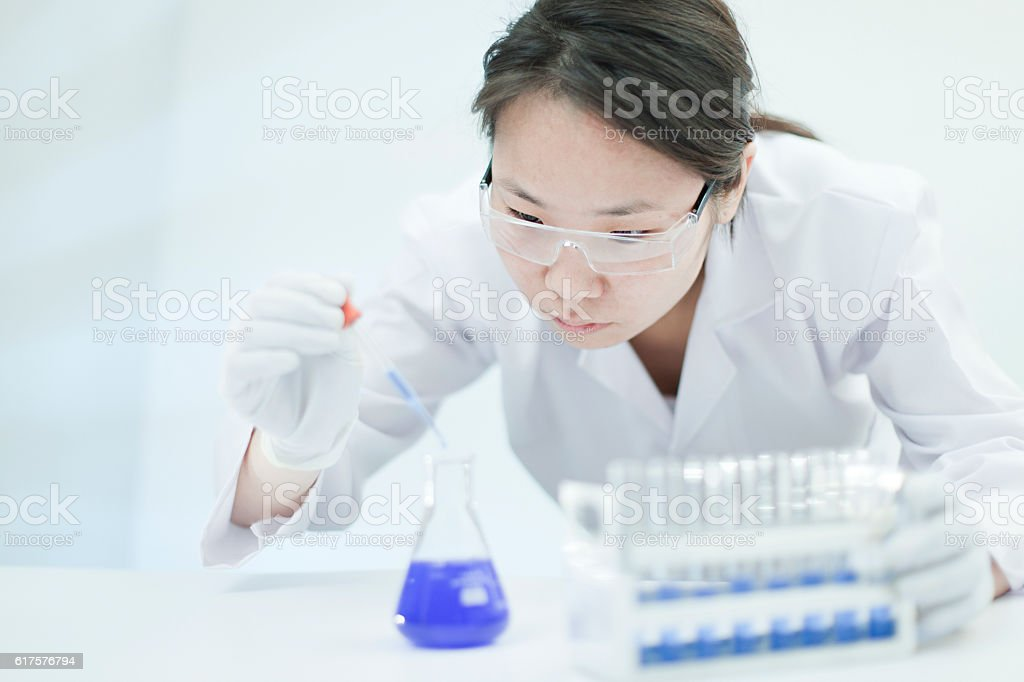 Asian woman scientist working with chemicals in a laboratory. stock photo