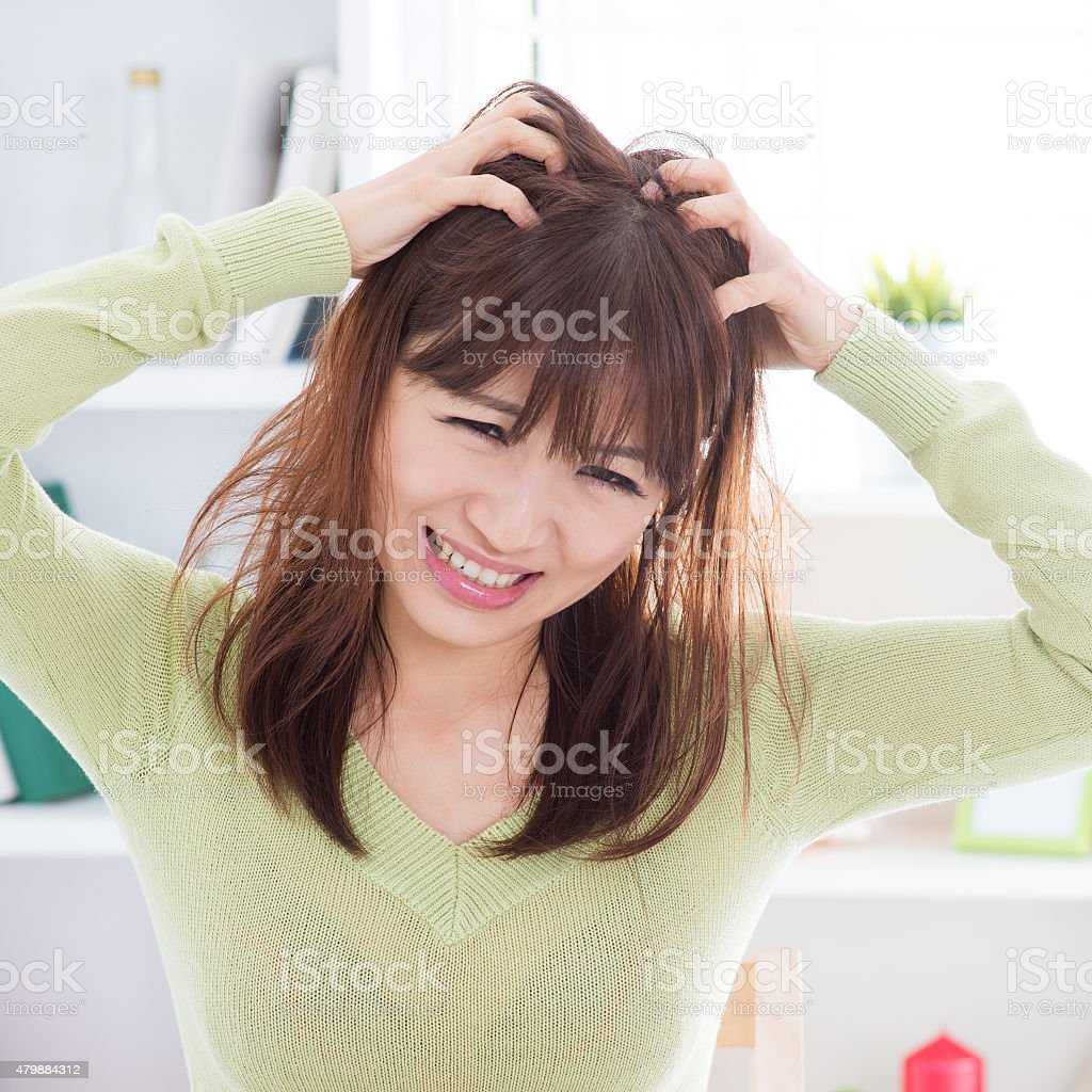Asian woman scratching itchy head stock photo