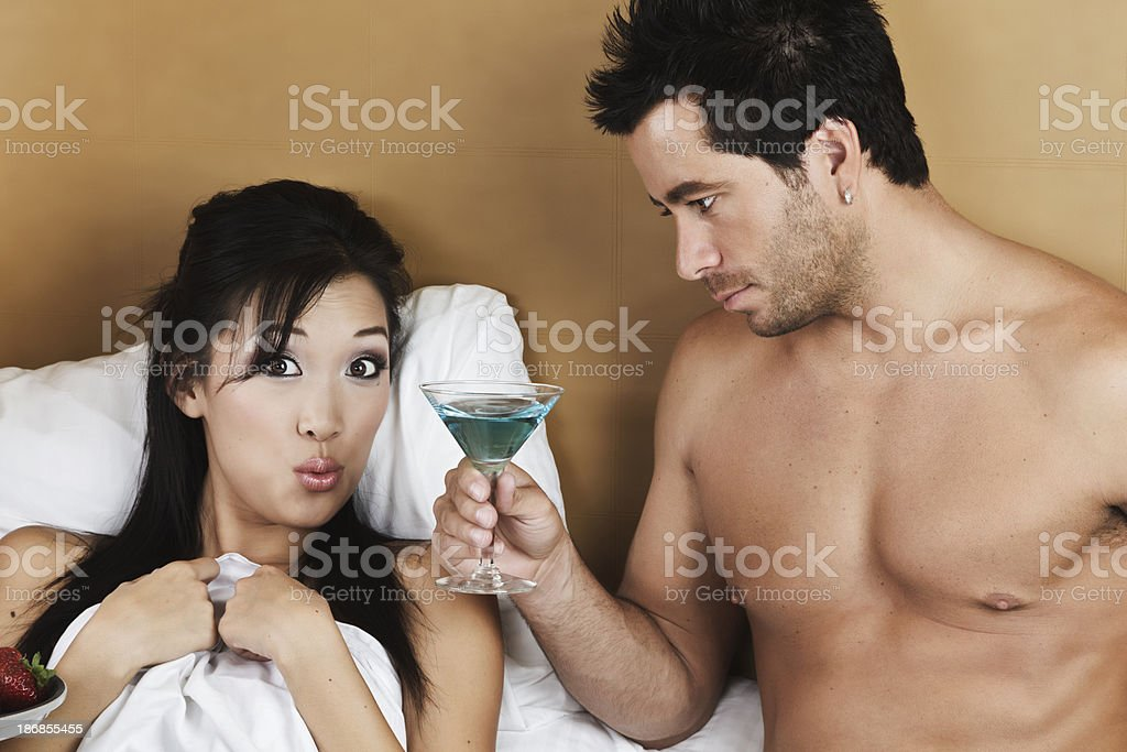 Asian Woman Served Martini in Bed By a Handsome Man royalty-free stock photo