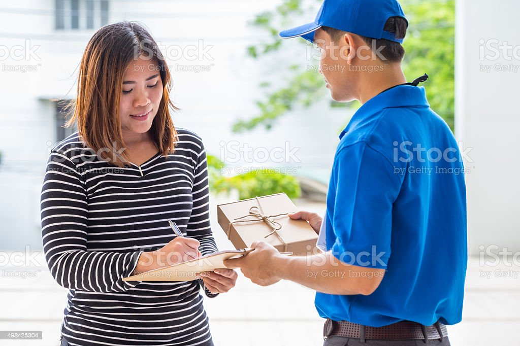 Asian woman signing receipt of delivered package stock photo