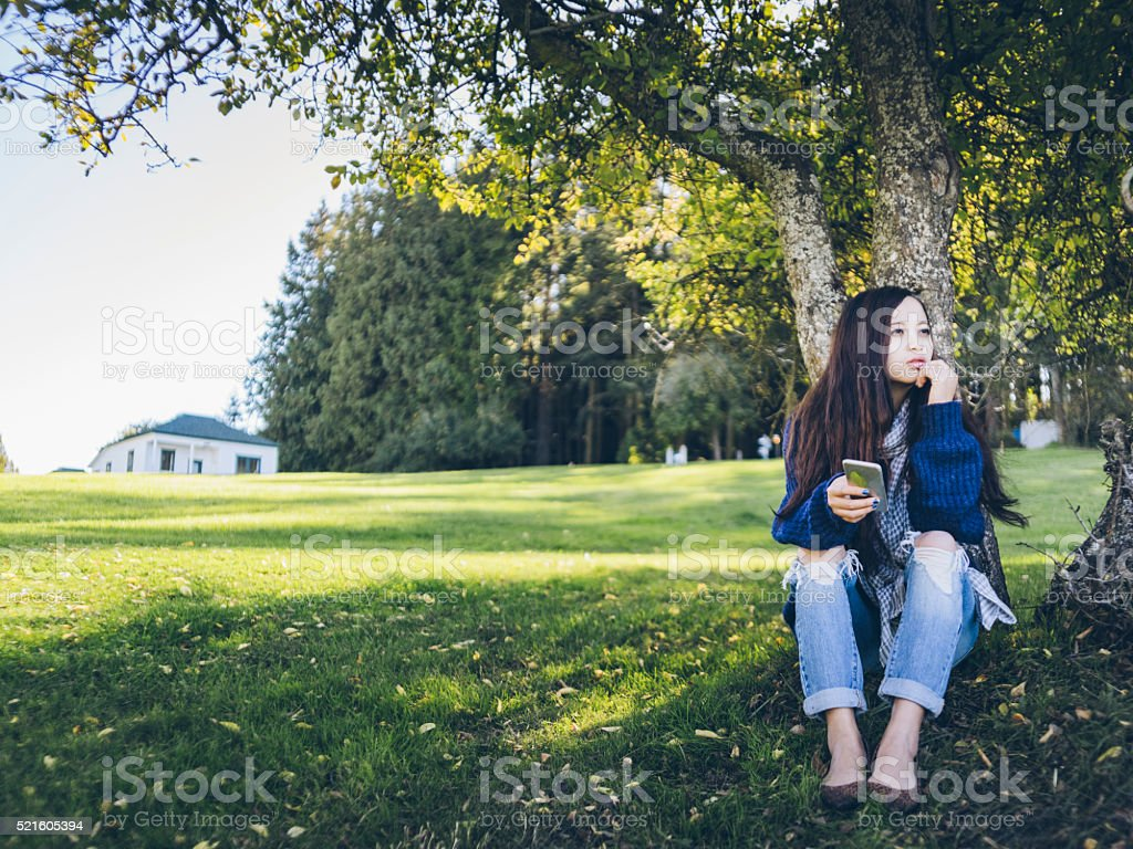 asian woman sitting at lawn holding cellphone stock photo